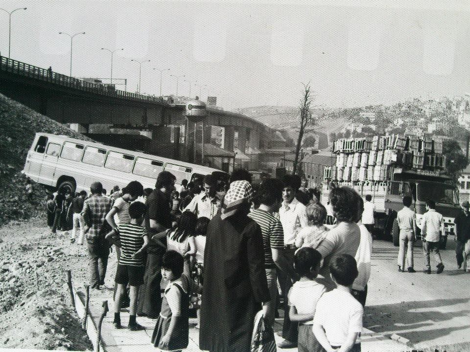 In the back ground can be seen the crashed bus and the bridge it rolled down from after the accident. Spain (circa 1975)
